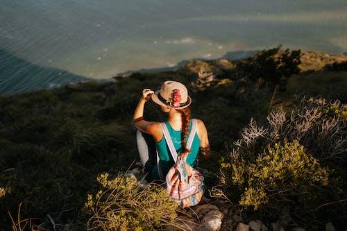 Faceless female tourist with rucksack enjoying lake from mount