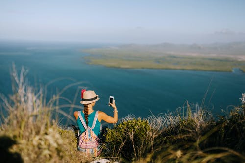 Back view of unrecognizable female traveler taking photo of foggy ocean on cellphone while resting on grass mount