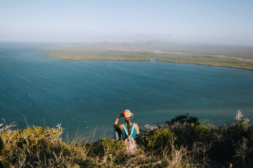 From above back view of anonymous female backpacker enjoying rippled ocean from mount under misty sky