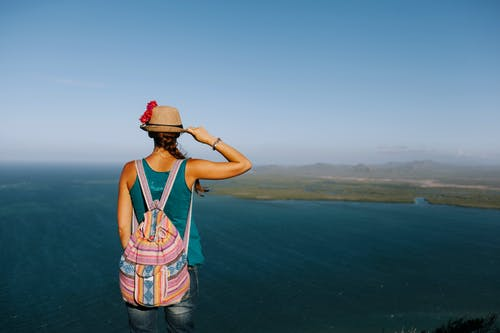 Back view of anonymous female tourist with rucksack touching straw hat while contemplating sea from mountain under blue foggy sky