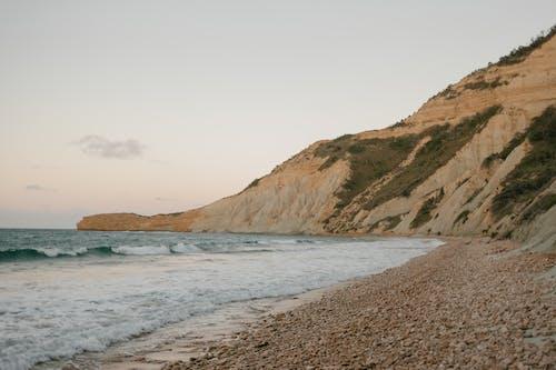 Montaña En La Playa Cerca Del Mar Ondulado Bajo El Cielo Nublado