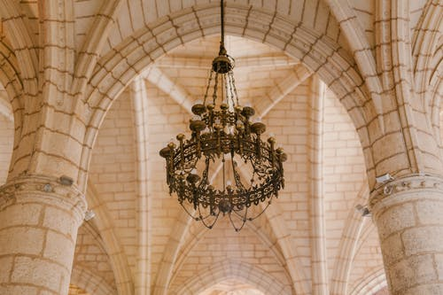 Old cathedral interior with ornamental chandelier on ceiling