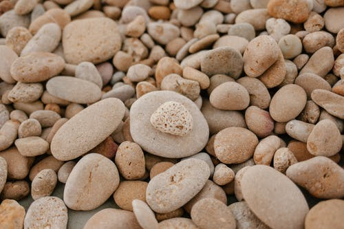 From above of textured background of small stones with blots on surface on shore