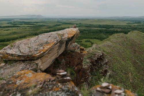 Rock rough cliff near grassy green valley