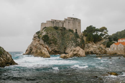Old castle located on rocky cliff covered with bushes