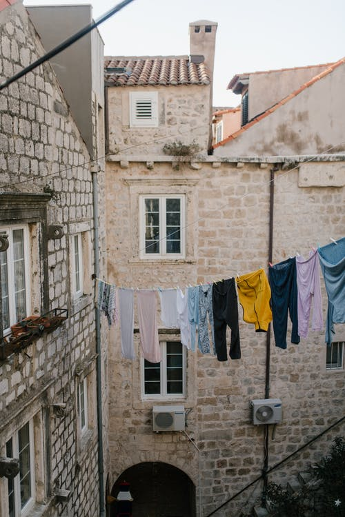 Clothesline with colorful apparel between old rough walls of houses with windows and arch in city