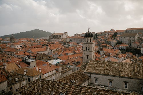 Cityscape of old town on hills with stone tower and various houses with tiled roofs in overcast weather