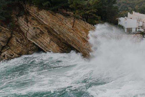 Foamy waves crashing on rocky cliff