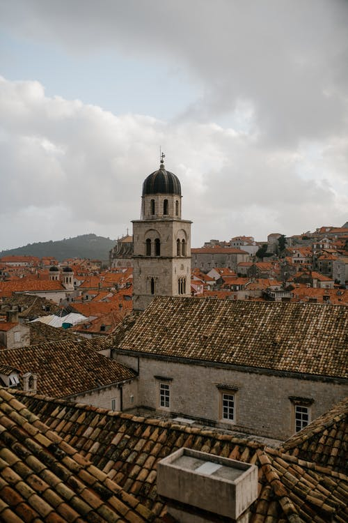 Residential buildings located around old tower of architectural monument Catholic church of Croatia under cloudy sky
