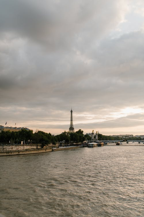 Cloudy sky over river washing shore of Paris with Eiffel Tower in overcast day