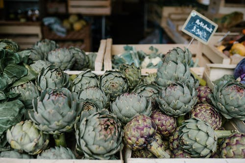 Ripe artichokes in boxes in market