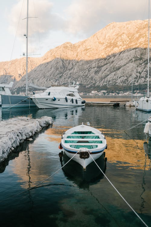 Boats and yachts moored on dock of lake