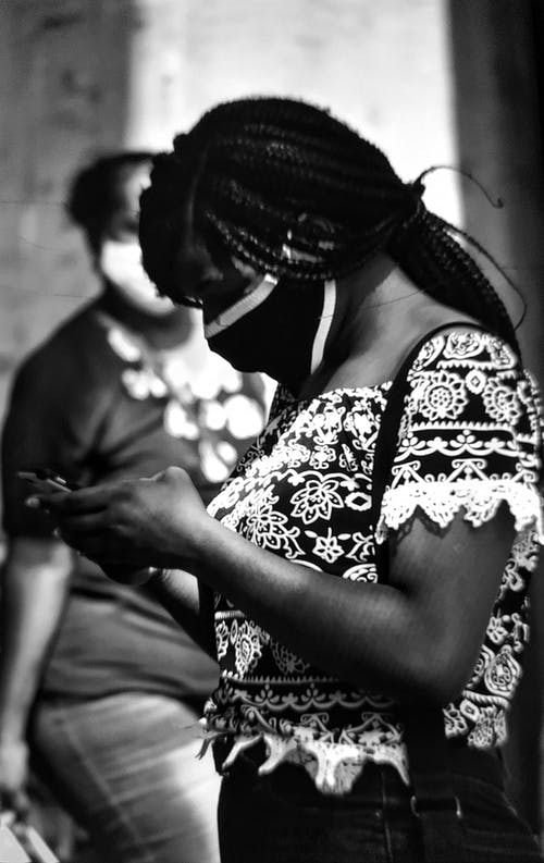 Grayscale Photo of a Woman Using a Smartphone