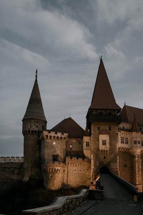 Facade of majestic ancient stone Corvin Castle in Gothic Renaissance style located beneath overcast dramatic sky in Romania