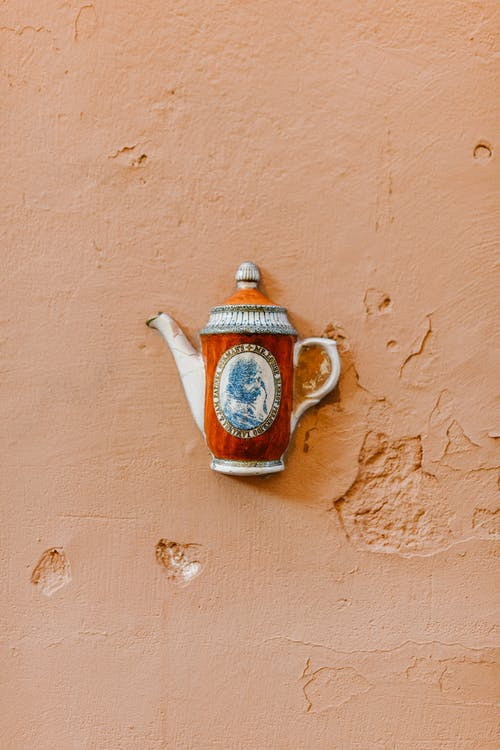Ornamental teapot placed on cracked concrete surface