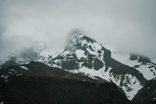 Scenic view of rough rocky mountains with slopes covered with snow and peaks in dense fog on overcast weather