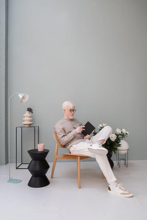 Chico Elegante Relajante En Silla Y Libro De Lectura En La Habitación Moderna