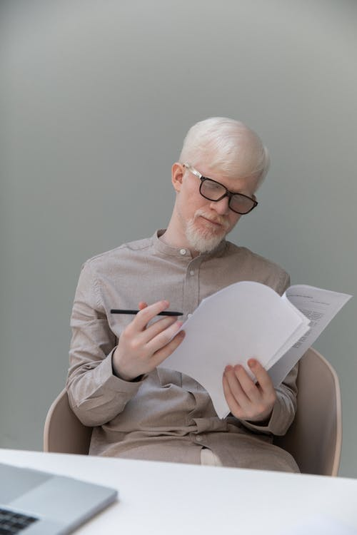 Young serious businessman in eyeglasses watching papers at table with laptop while working on project on gray background