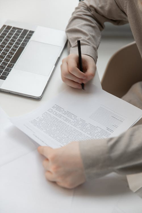 Faceless male worker with paper document near laptop on desk