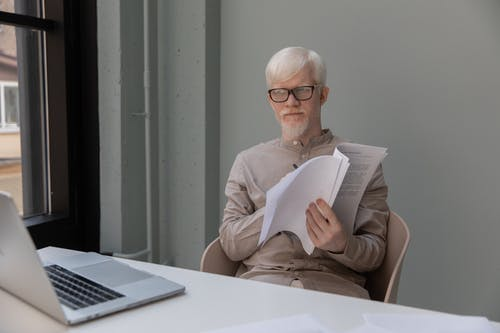 Serious office worker with papers watching laptop at table