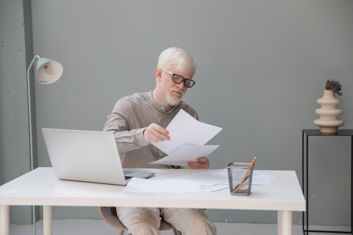 Albino concentrated office worker in eyeglasses watching documents at desk with netbook in daylight