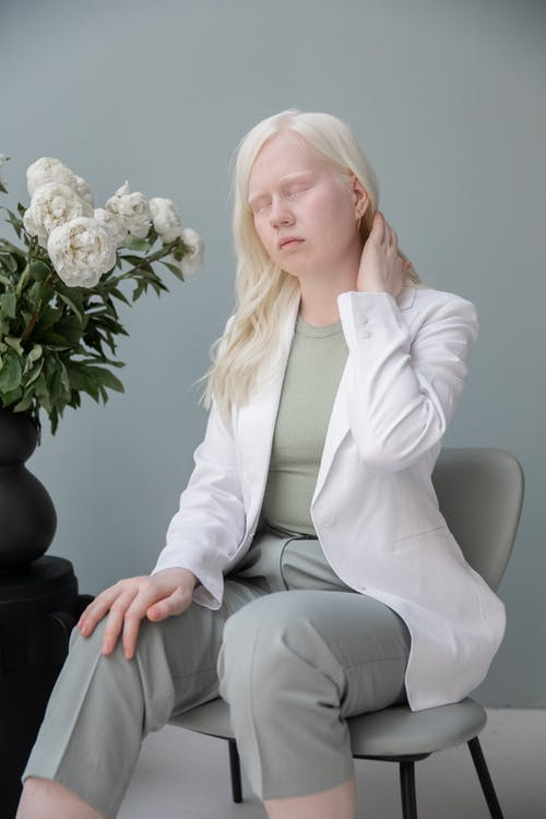 Disappointed young female with closed eyes touching neck while sitting on chair near white blooming flowers