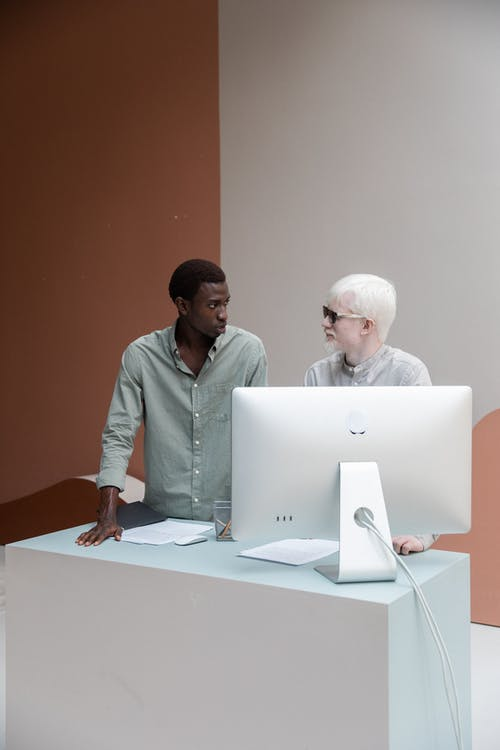 Black man with albino colleague standing near computer and looking at each other while having conversation about work in creative office