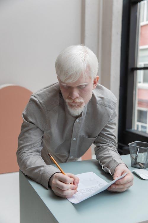 Busy albino man writing in document