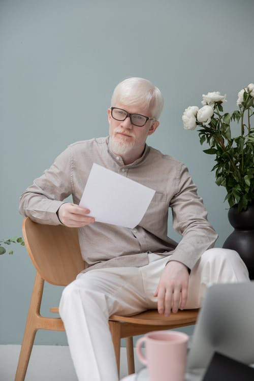Serious albino man sitting with papers