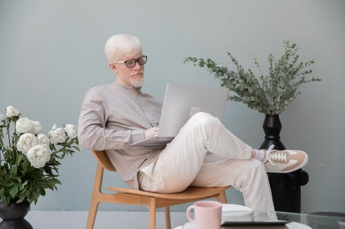 Busy albino man browsing laptop in room