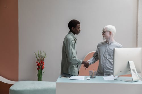 Side view of African American man shaking hand of albino male coworker while standing near table with computer in modern office
