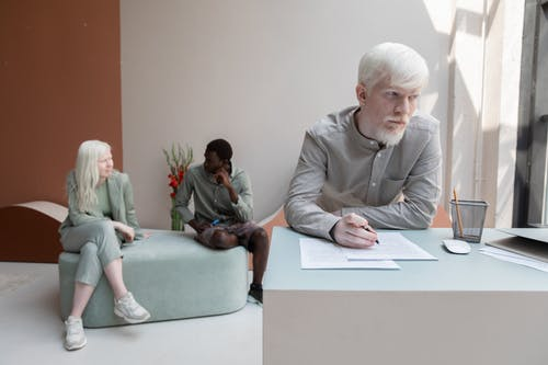 Albino worker standing at table and writing on paper in office with African American man sitting with woman on background