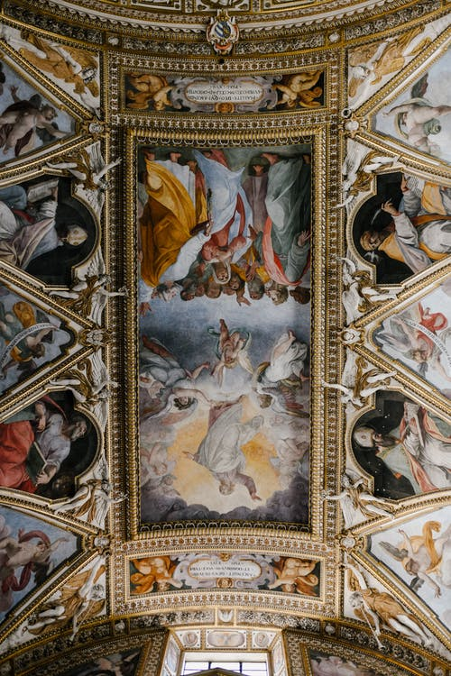 From below dome ceiling covered with majestic colorful fresco paintings in Baroque style in Catholic cathedral