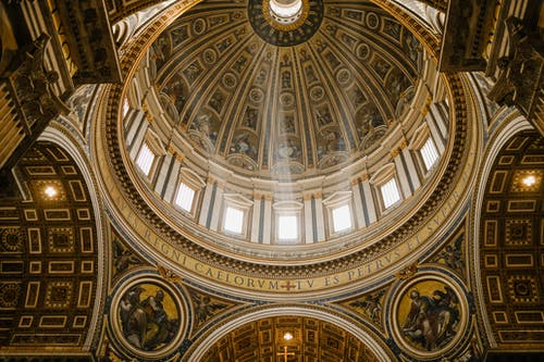 Low angle impressive design of dome with fresco paintings and golden ornamental elements in famous Catholic Saint Peters Basilica in Rome