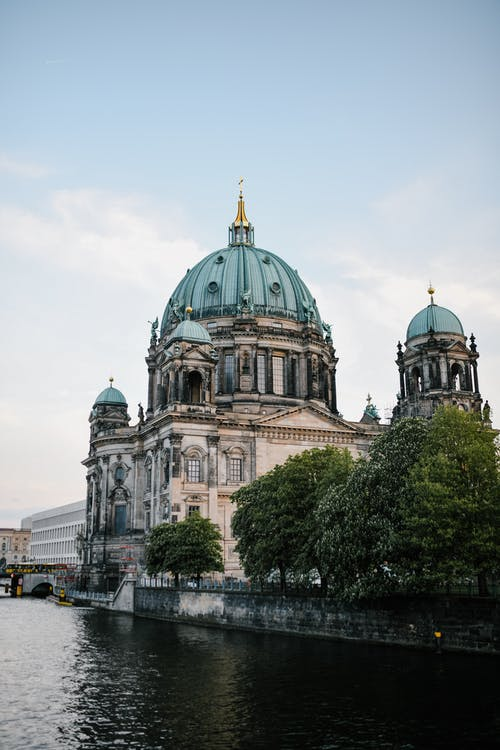 Exterior of impressive Berlin Cathedral with green sandstone dome built in Neo Renaissance style on rippling river coast under blue sky