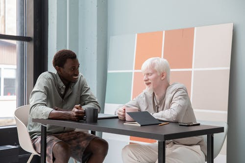Cheerful African American man and albino colleague sitting at table with cups of coffee in modern workspace while having conversation about work