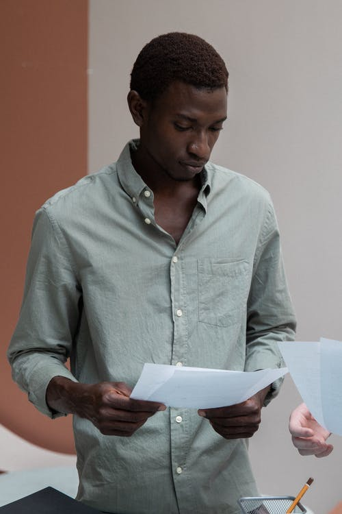 Focused African American male in shirt reading papers while standing against wall in creative office during work in modern workplace