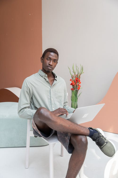Serious black man with laptop in office