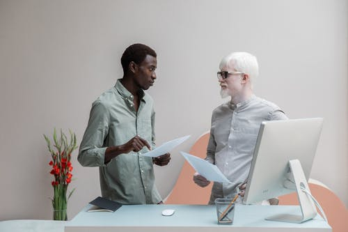 Focused African American man and albino male colleague standing near table with computer and documents in hands while discussing work and looking at each other