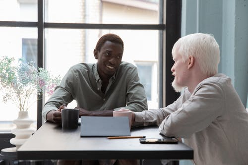 Cheerful African American man sitting at table with albino coworker while drinking coffee and talking about work in modern office