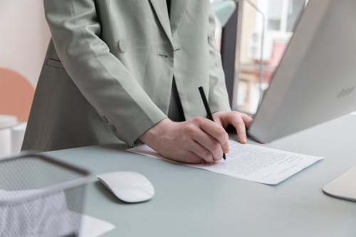 Unrecognizable worker standing at table with computer while taking notes in document while working in office