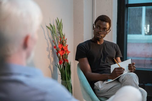 Attentive black man writing in notebook while sitting with client