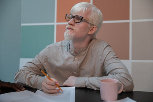Serious albino man with documents in office