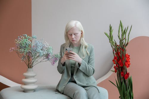 Young Albino woman messaging on smartphone