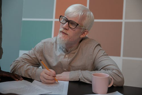 Albino man signing documents in office