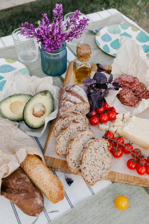 Нарезанный хлеб на белой бумаге рядом с нарезанным огурцом и красным виноградом на коричневой деревянной разделочной доске