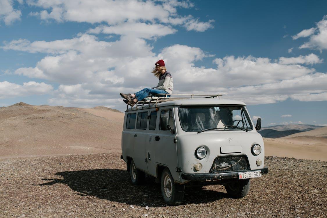 Full length of anonymous female traveler sitting on roof of van in desert under cloudy sky