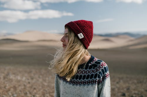 Side view of young female in casual warm sweater and red knitted hat standing in dry desert