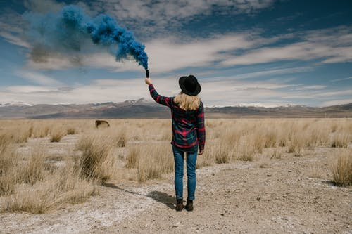 Young woman with colored smoke in desert