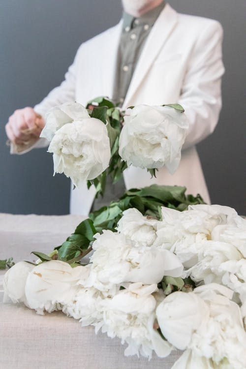 Crop anonymous male florist in suit arranging flowers on table while creating floral bunch in room
